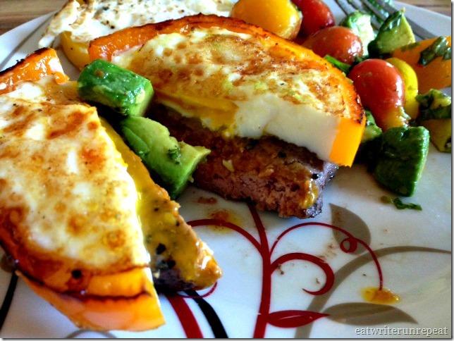 hamburger patty with fried egg and avocado tomato salad